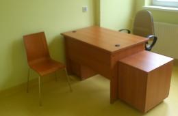 Biurka dla lekarzy, z kontenerem, szufladą na klawiaturę, szafką na PC oraz krzesłem obrotowym obszytym tkanina zmywalną. Dodatkowo w skład zestawu włączono krzesło sklejkowe dla pacjentów